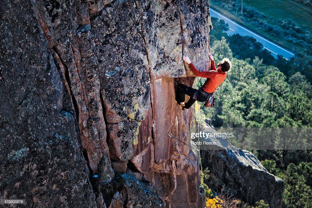 A male rock climber ascends a granite wall in Colorado : Stock Photo