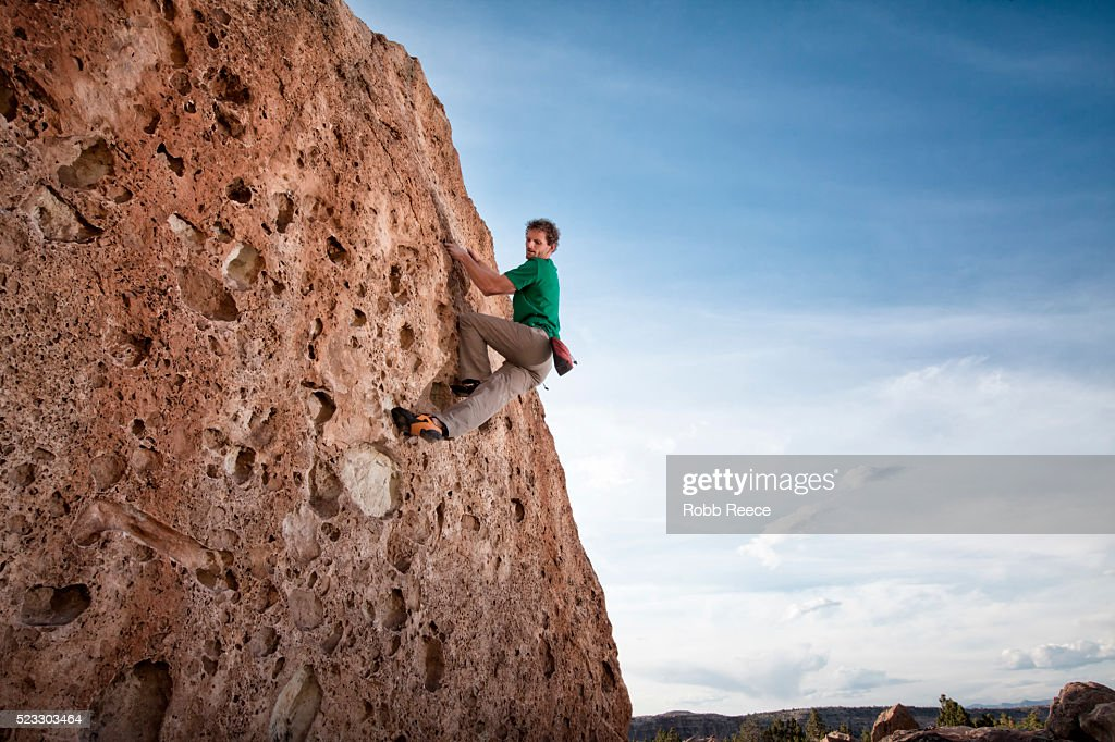 A male rock climber ascends a sandstone boulder in Colorado : Stock Photo