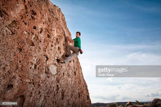 a male rock climber ascends a sandstone boulder in colorado - robb reece stock pictures, royalty-free photos & images