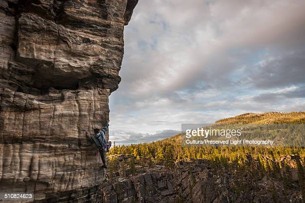Male rock climber, climbing a rock wall at Boulder Fields, South Okanagan Valley, Kelowna, British Columbia, Canada
