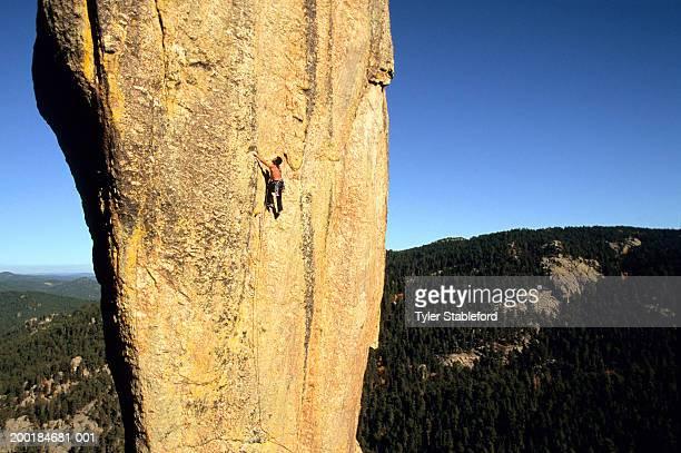 male rock climber climbing on granite spire - felsspitze stock-fotos und bilder