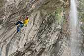 Male rock climber fixing the security rope in quickdraws