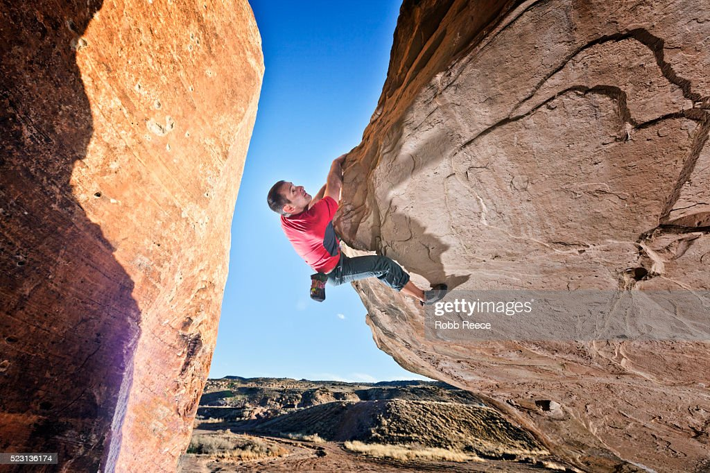 A male rock climber on a sandstone boulder : Stock Photo
