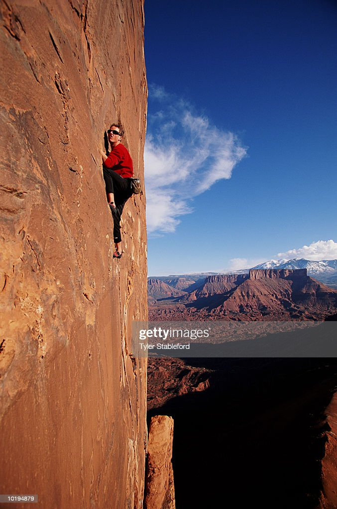 Male rock climber on sheer cliff face : Stock Photo