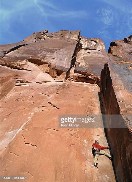 Male rock climber on sheer sandstone rock face, low angle view