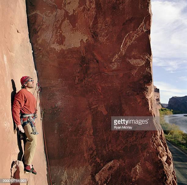 Male rock climber on sheer sandstone rock face, side view