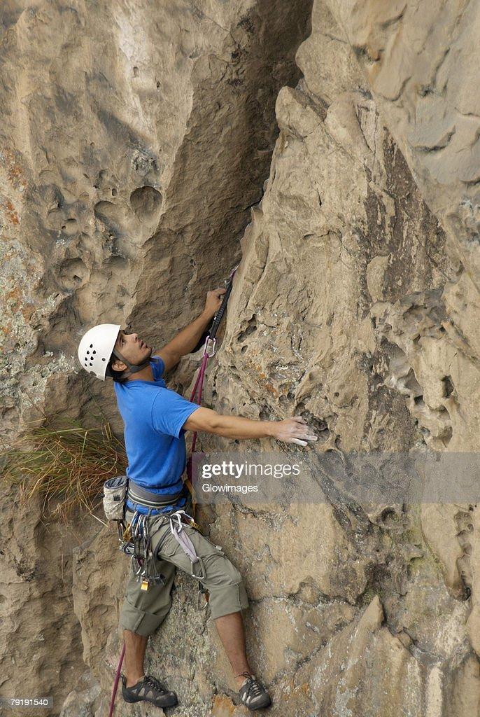 Male rock climber scaling a rock face : Foto de stock