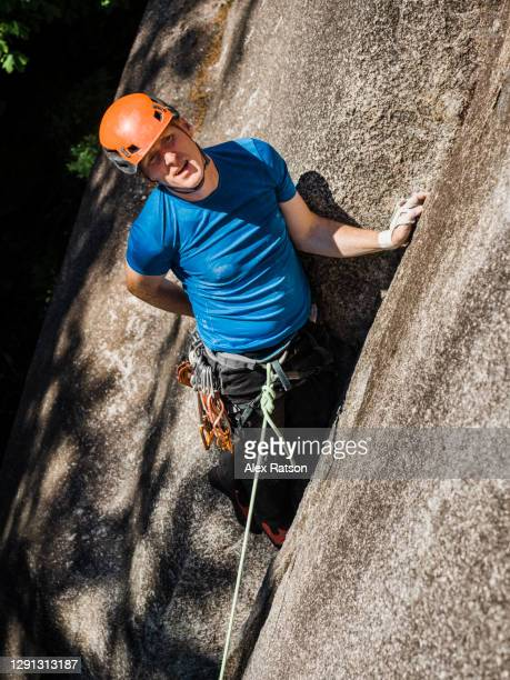 a male rock climber takes a break while ascending a blank granite slab in the squamish smoke bluffs and dips his hand in a chalk bag - chalk bag stock pictures, royalty-free photos & images