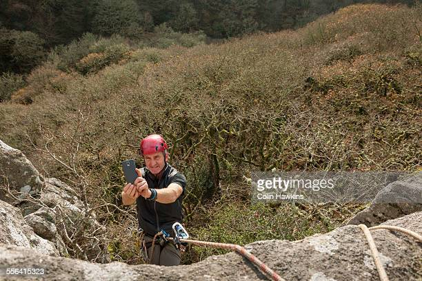 Male rock climber taking photo with smartphone