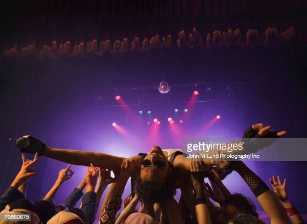 Male rock star crowd surfing