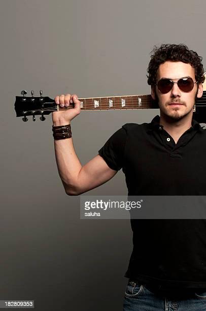 Male rockstar wearing black, holding guitar behind his head