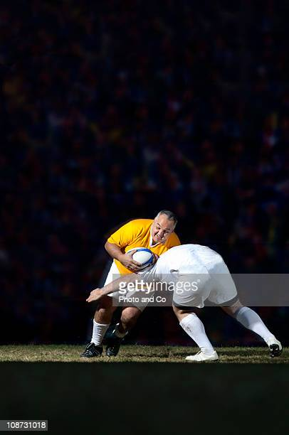 male rugby player being tackled by opponents