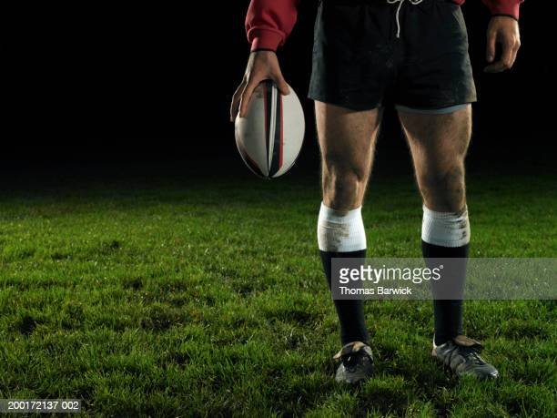 Male rugby player holding ball, night, low section
