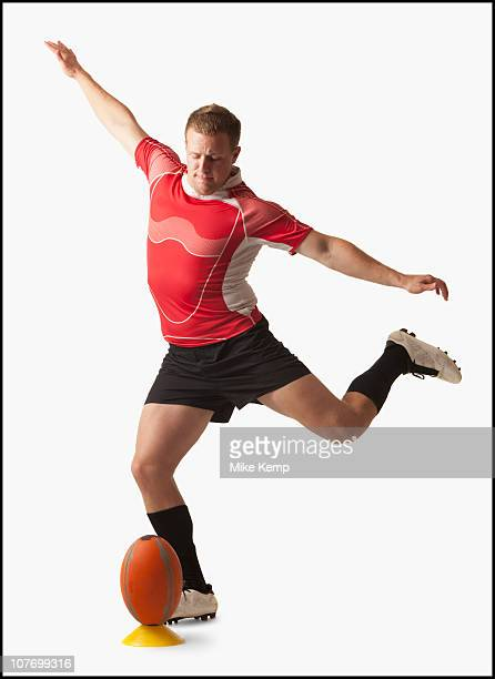 Male rugby player kicking ball