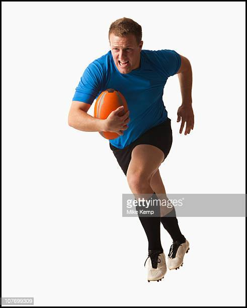 Male rugby player running with ball