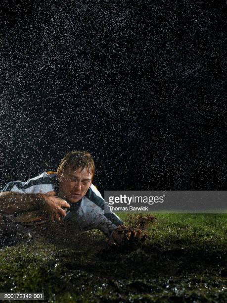 male rugby player with ball in mud on ground, night - try scoring stock pictures, royalty-free photos & images