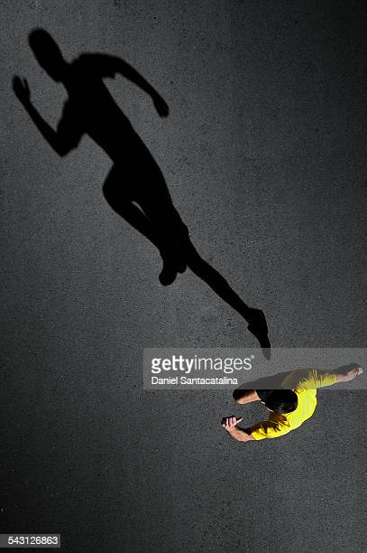 A male runner and his shadow