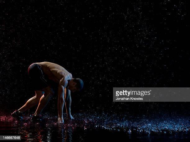 Male runner at start in rain