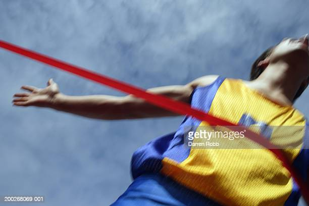 male runner breaking tape, crossing finish line (blurred motion) - ゴールライン ストックフォトと画像