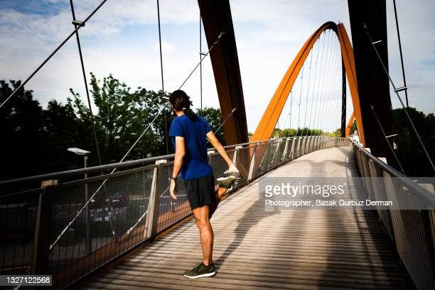 a male runner doing standing quad stretch and his shadow on a bridge - stretching stock pictures, royalty-free photos & images