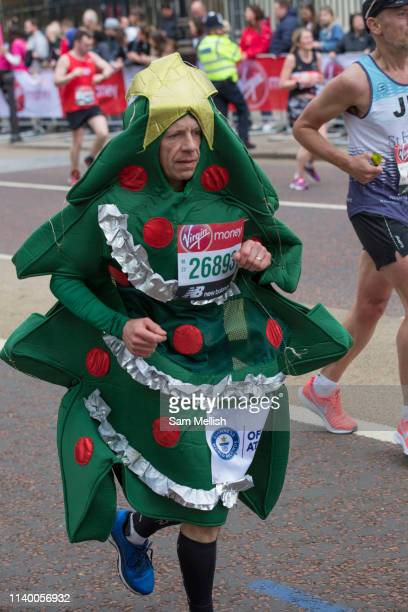A male runner dressed as a Christmas tree on Birdcage Walk during The Virgin London Marathon on 28th April 2019 in London in the United Kingdom Now...