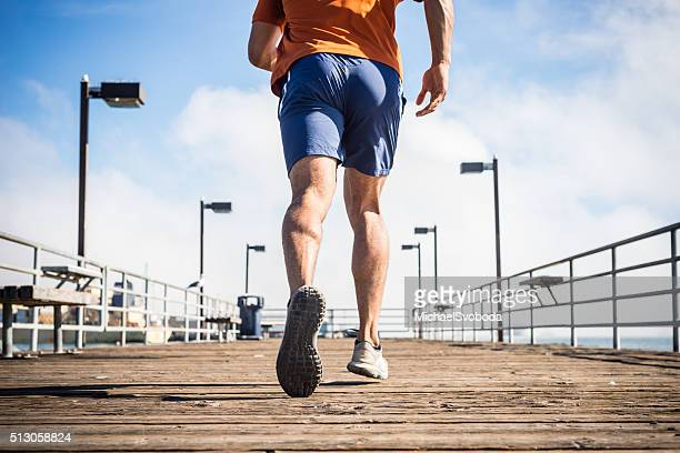 male runner jogging on a ocean pier - striding stock pictures, royalty-free photos & images