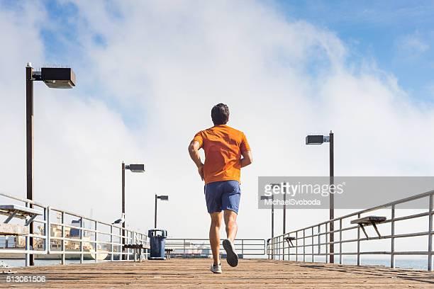 Mâle coureur Faire du jogging sur une jetée sur l'océan