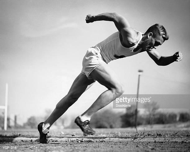 Männliche Läufer springen von Startblöcken zu Beginn des Rennens