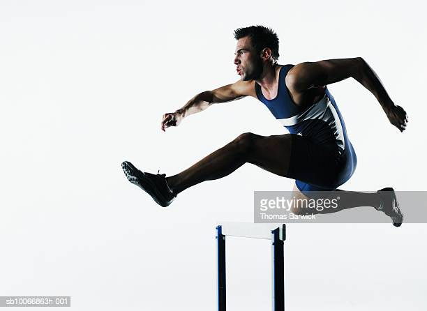 Male runner jumping over hurdle