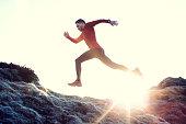 Male runner leaps through sunlit grassy landscape