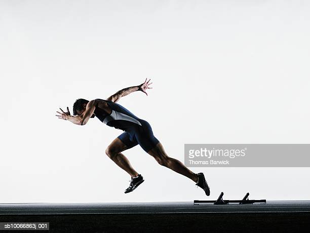 male runner leaving starting block, side view - athletics stock photos and pictures