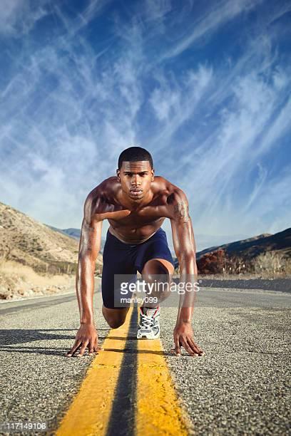 Male runner on desert road ready to run