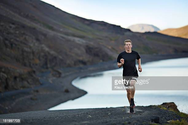 Male runner on mountain road, lake in background