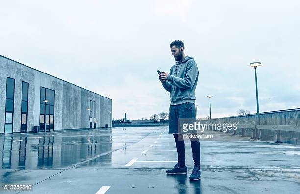 Male runner plays with smart phone before run
