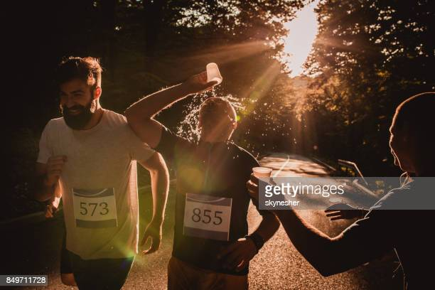 Male runner refreshing himself and pouring water on the face at sunset.