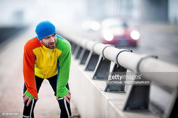 Male runner resting on the bridge