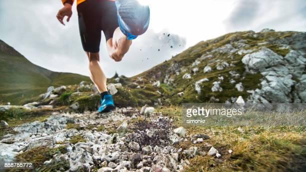 Männliche Läufer läuft über die Wiese hoch im Gebirge