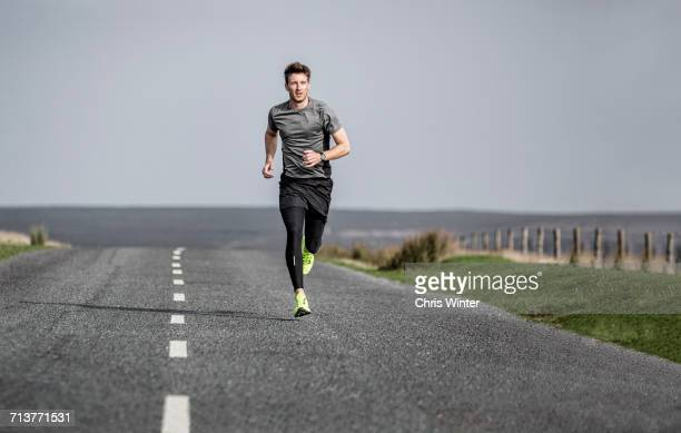 male runner running along rural moorland road - gray pants stock pictures, royalty-free photos & images