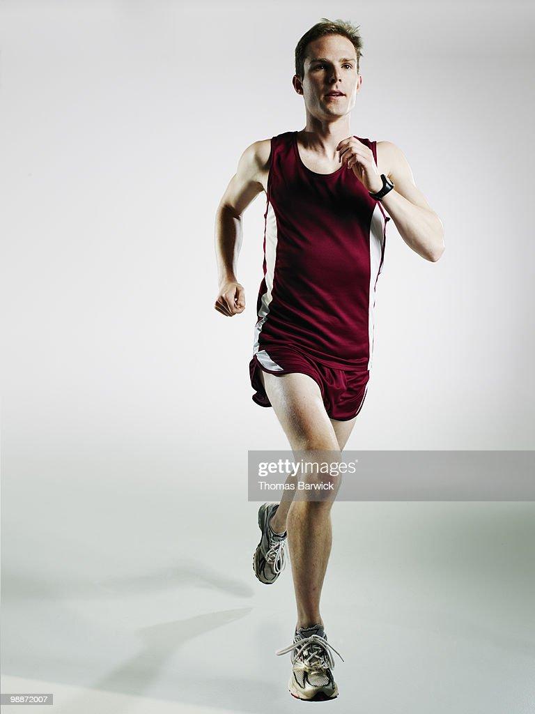 Male runner running mid stride on white background : Foto de stock