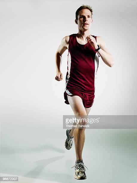 Male runner running mid stride on white background