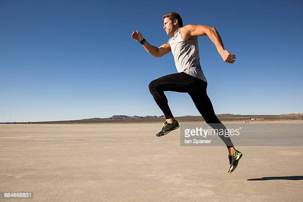 male runner running on dry lake bed, el mirage, california, usa - chándal fotografías e imágenes de stock