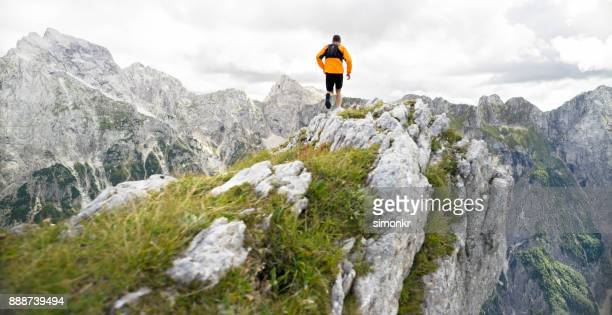 Male runner running on edge of cliff with beautiful view