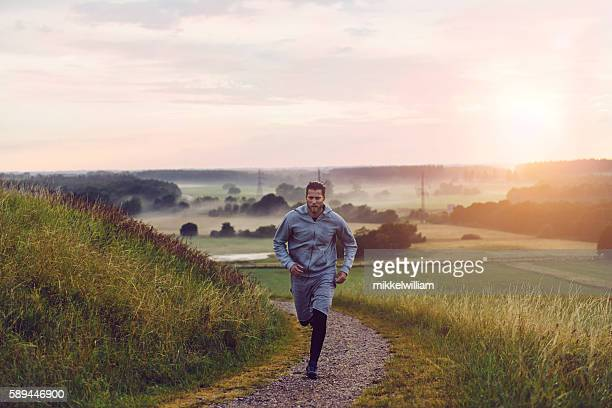 Male runner runs outside in nature at sunset