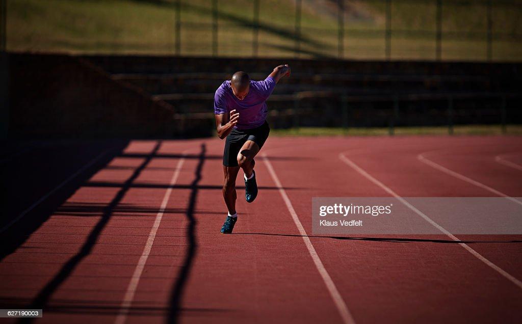 Male runner sprinting at stadium : Stock Photo