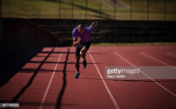 male runner sprinting at stadium - training course stockfoto's en -beelden
