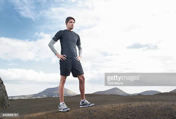 Male Runner standing in barren landscape