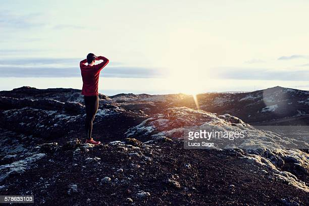 Male runner stands and looks into distant scenery