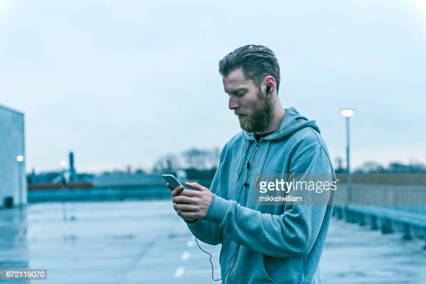 male runner stands outside with mobile phone - hood clothing stock photos and pictures