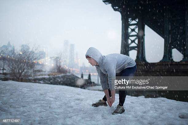 Male runner stretching in snow, Brooklyn, New York, USA