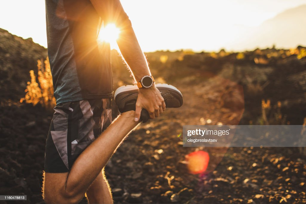 Male runner stretching leg and feet and preparing for running outdoors. Smart watch or fitness tracker on hand. Beautiful sun light on background. Active and healthy lifestyle concept. : Stock Photo